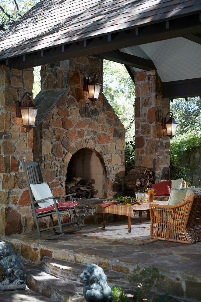 a rustic patio with a stone fireplace and pillars, rattan and wooden furniture and colorful textiles  (We Got Lites)
