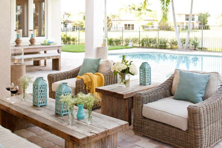 a small rustic patio with wicker ad wooden furniture and aqua touches by the pool  (Krista + Home)