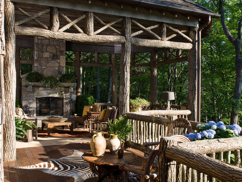 a rustic patio done with logs and a stone fireplace, wooden furniture, potted greenery and blooms  (William T Baker)