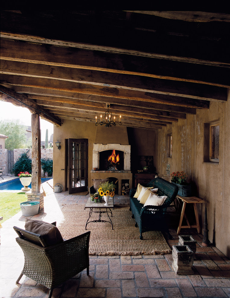 a rustic covered patio with wooden beams, painted wicker furniture and a fireplace looks like an outdoor living room  (Don Ziebell)