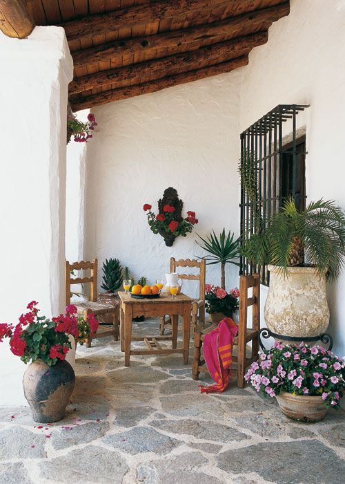 a Mediterranean rustic patio with a stone floor and walls, a wooden ceiling, potted greenery and blooms and wooden furniture