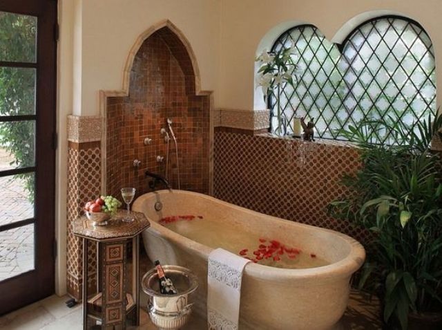 a Moroccan bathroom with catchy tiles, an Eastern-shaped niche, a stone bathtub, a carved side table and potted greenery