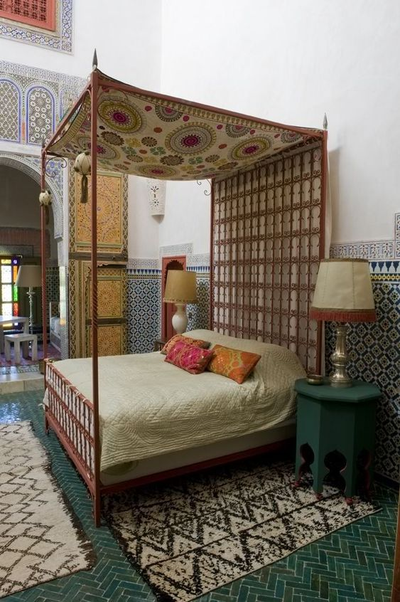 a Moroccan bedroom all clad with traditional tiles, with rugs, carved furniture and boho rugs and bedding