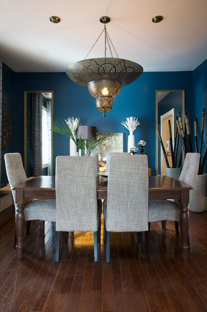 a Moroccan dining room with blue walls, a long table, upholstered chairs, a pendant lamp and a duo of mirrors