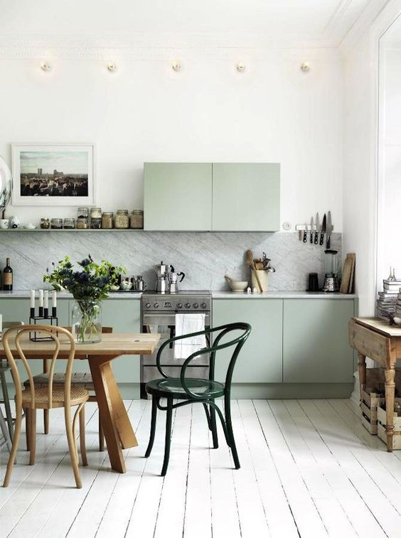 a Nordic kitchen with green cabinets, white stone countertops and a backsplash, a wooden table and vintage chairs