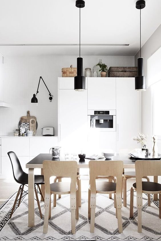 a Nordic kitchen with sleek white cabinets, black lamps, a black table and plywood chairs