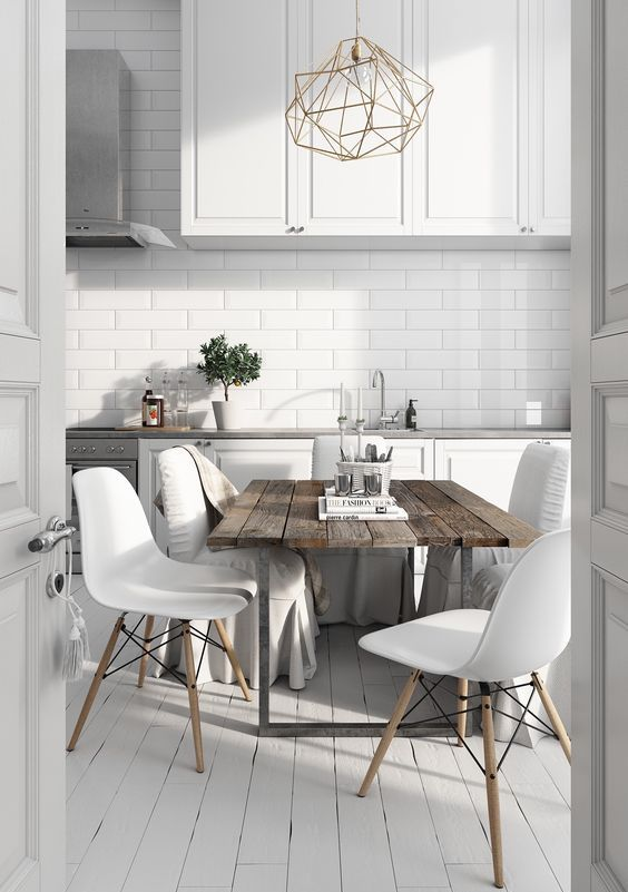 a Nordic kitchen with white cabinets and tiles, a rough wooden table, modern white chais and a geometric chandelier