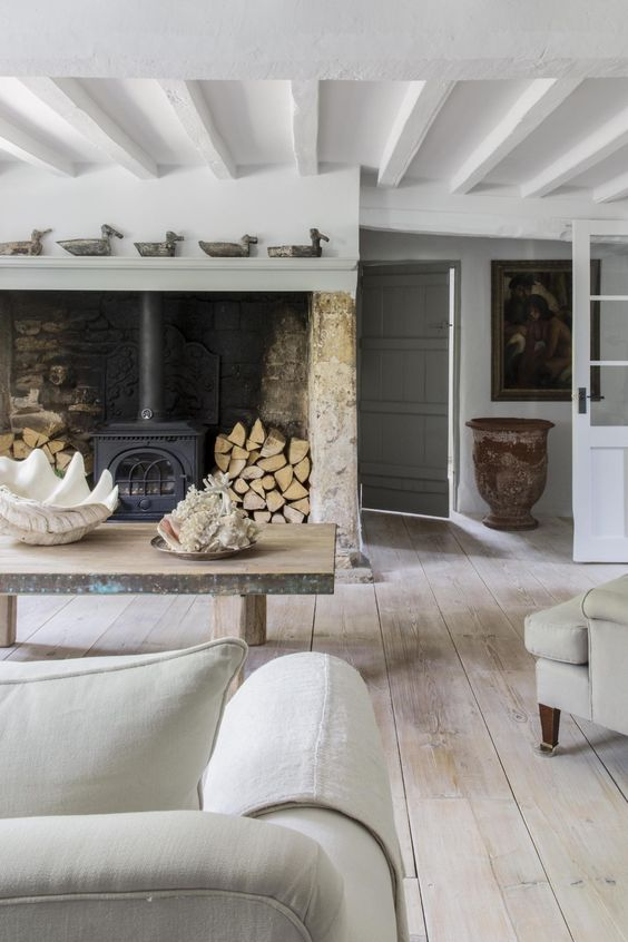 a Provence living room with a hearth with firewood, a rough wooden table and a whitewashed wooden ceiling