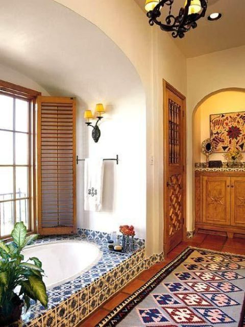 a bathroom with a Moroccan rug and blue and white tiles and shutters on the window