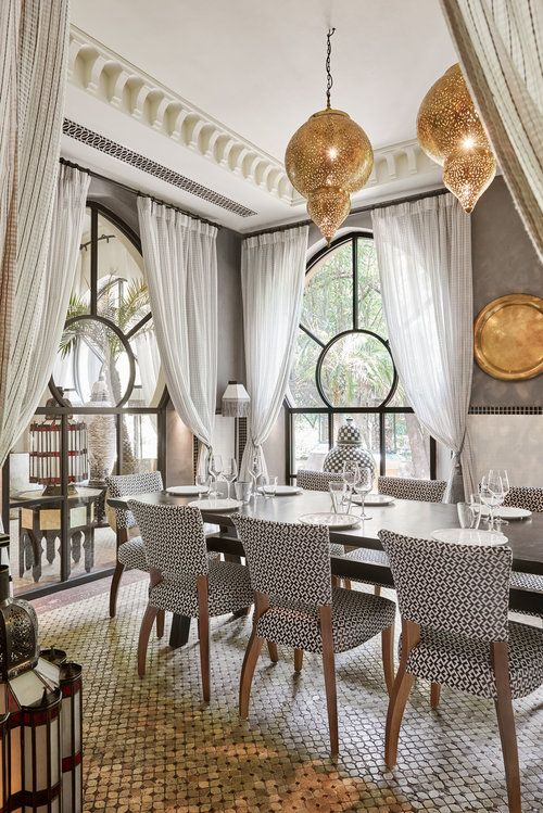 a beautiful Moroccan dining space done in neutrals, with grey walls, a long table with printed chairs, a patterned floor and metal pendant lamps