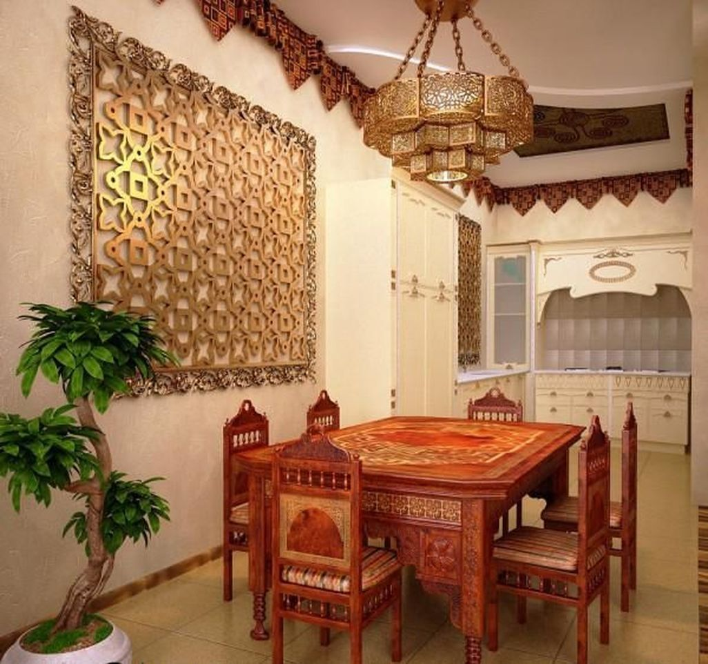 a beautiful dining room with heavy carved Moroccan furniture, a beautiful metal pendant lamp and a laser cut artwork