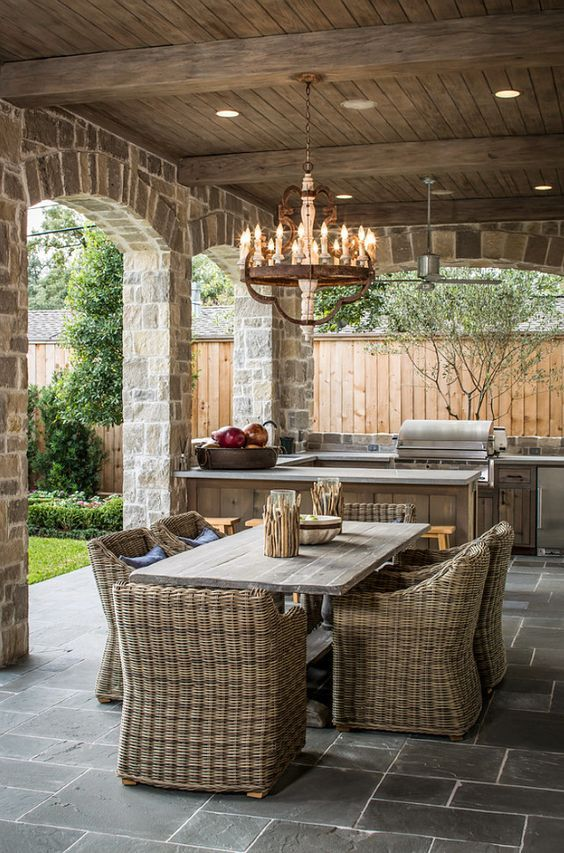 a beautiful rustic patio with wooden and wicker furniture, a wooden chandelier and stone pillars