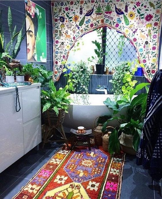 a boho Moroccan bathroom with a colorful curtain, a brugth rug and artwork and lots of potted greenery
