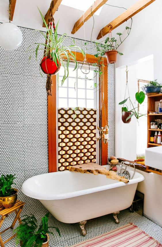 a boho bathroom done with penny tiles, a geometric screen, potted greenery, a clawfoot tub and living edge caddy