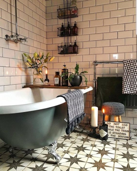 a boho bathroom done with pretty Moroccan tiles, potted plants and blooms, candles and a green clawfoot tub