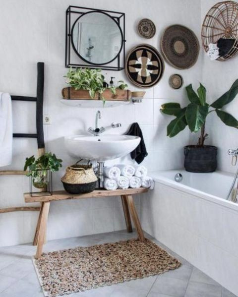 a boho bathroom with decorative baskets, a crochet rug, baskets for storage and potted plants