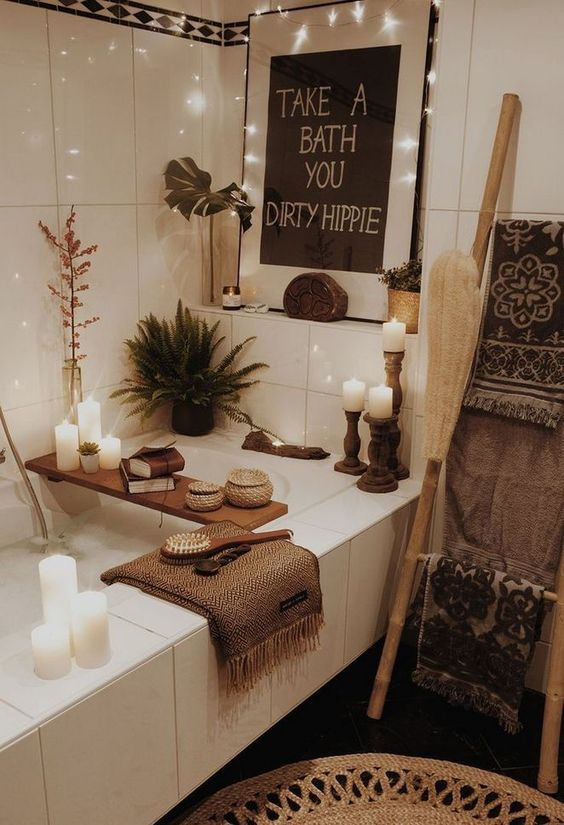 a boho bathroom with lights, an artwork, a wooden caddy, lots of candles and jute touches