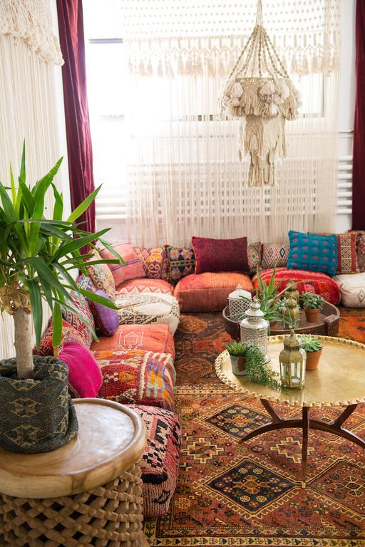 a boho living space with floor cushions and pillows instead of a sofa, rugs and pendant lamps