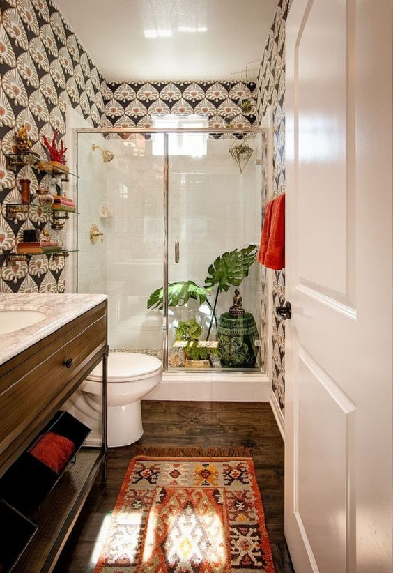 a boho meets art deco bathroom with catchy wallpaper, a boho rug, greenery and a painted side table