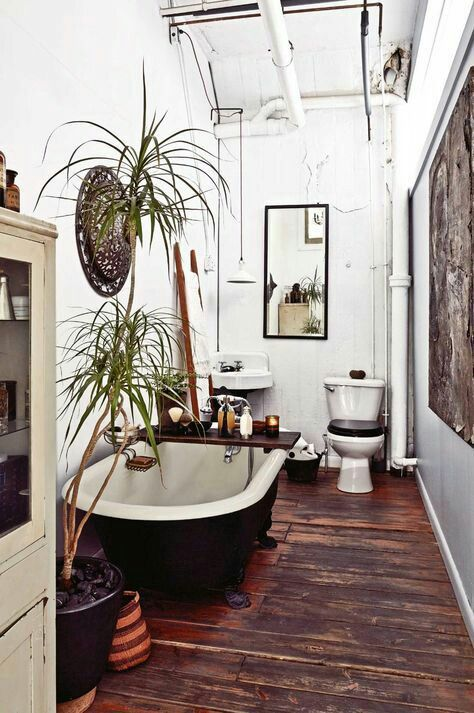 a boho meets rustic bathroom with a stained floor, a black tub, potted greenery, a decorative basket, vintage appliances