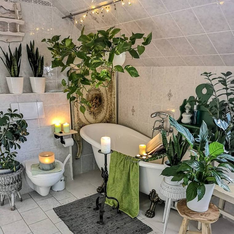 a boho oasis with lots of potted greenery, candles, lights and a clawfoot bathtub plus baskets