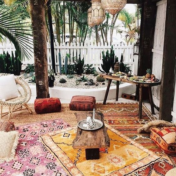 a boho patio with colorful printed rugs, cushions, ottomans, rattan and wooden furniture, Moroccan lanterns