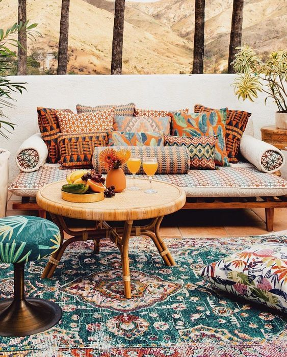 a boho patio with rattan and wooden furniture, printed pillows and rugs plus cushions and ottomans