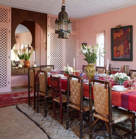 a bold Moroccan dining space with pink walls, a long table with a red tablecloth, woven chairs and a bold pendant lamp