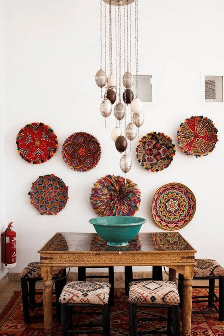 a bold Moroccan dining zone with a carved wooden table, printed stools, decorative plates on the wall and pendant lamps hanging on chains