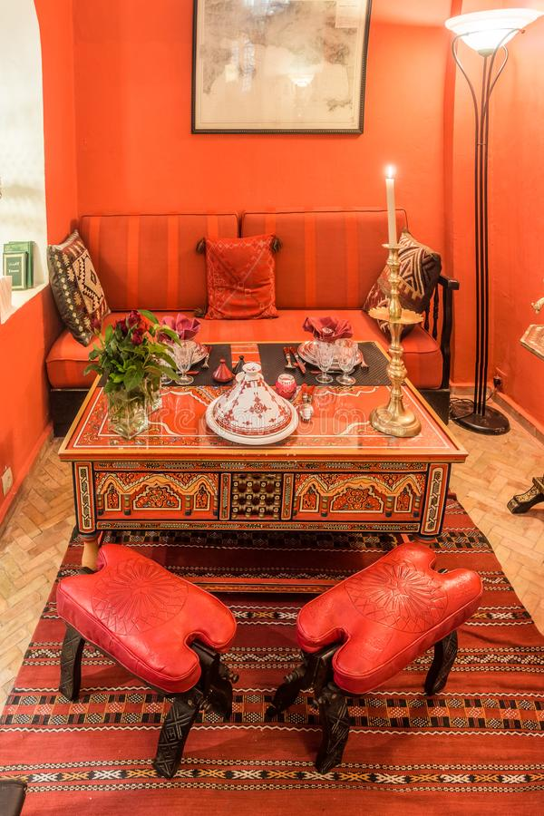 a bold red Moroccan dining space with red walls and furntiure, a carved and painted wooden table, a printed rug and a lovely lamp