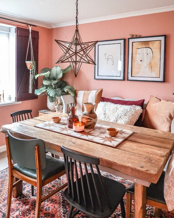 a bright Moroccan dining room with coral walls, a wooden table, mismatching chairs and pillows and a beautiful star-shaped pendant lamp