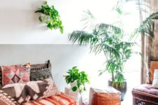 a bright Moroccan living room with colroful textiles, potted plants, a fabric ceiling and a leather ottoman