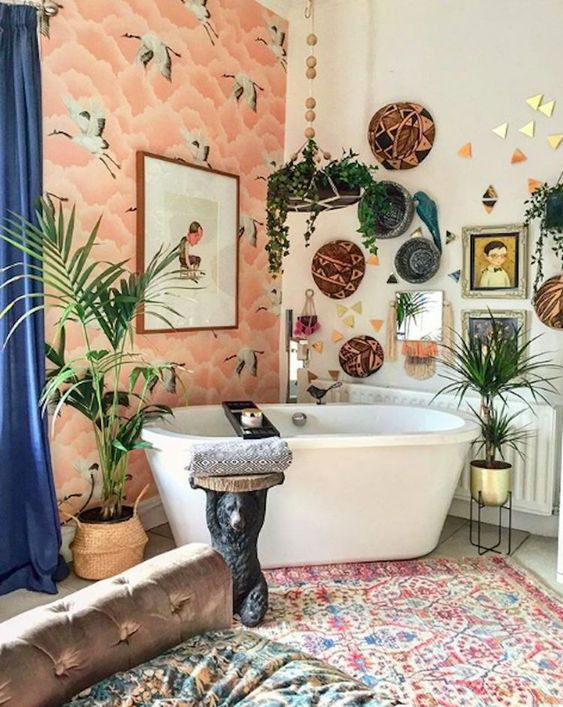 a bright bathroom with a wallpaper wall, boho rugs, decorative baskets, potted plants and artworks