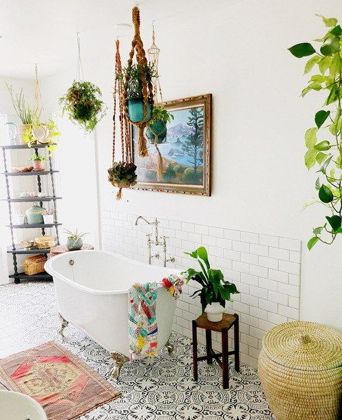a bright boho bathroom with a mosaic tile floor, boho rugs and towels, potted plant,s a clawfoot tub and an etagere