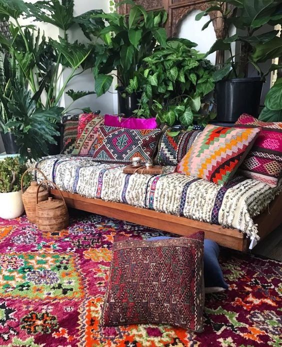 a bright boho patio with a wooden bench with printed and colorufl upholstery, bright pillows, potted greenery and baskets with lids