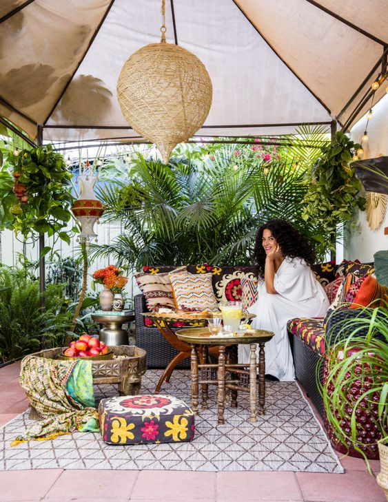 a bright boho patio with colorful pillows, tetiles, woven lamps and a wooden coffee table plus lots of greenery