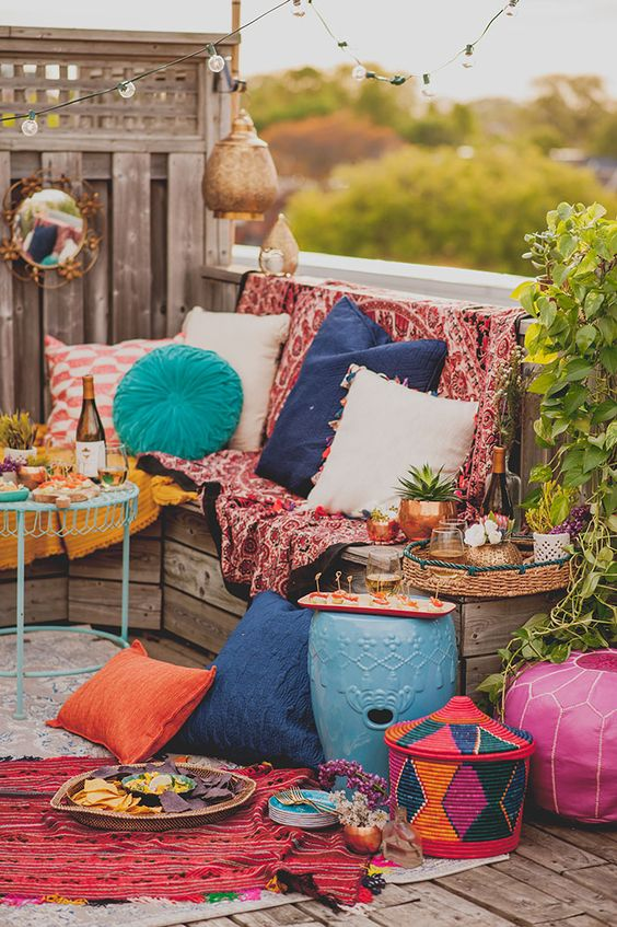 a bright boho patio with colorful textiles, rugs, pillows, Moroccan lanterns, woven baskets and colorful side tables