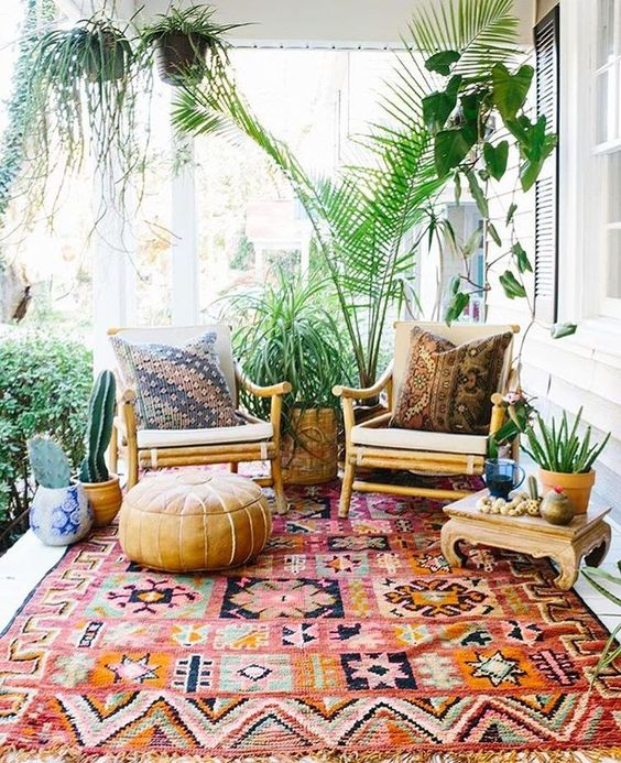 a bright boho patio with rattan furniture, a wooden low table, a leather ottoman, potted plants and cacti