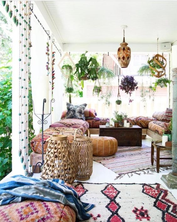 a bright boho patio with wooden and metal lanterns, rattan lamps on the floor, colorful and printed textiles, rugs and pillows