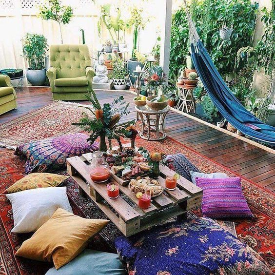 a bright boho space with a blue hammock, bright furniture and cushions, a pallet table and potted greenery