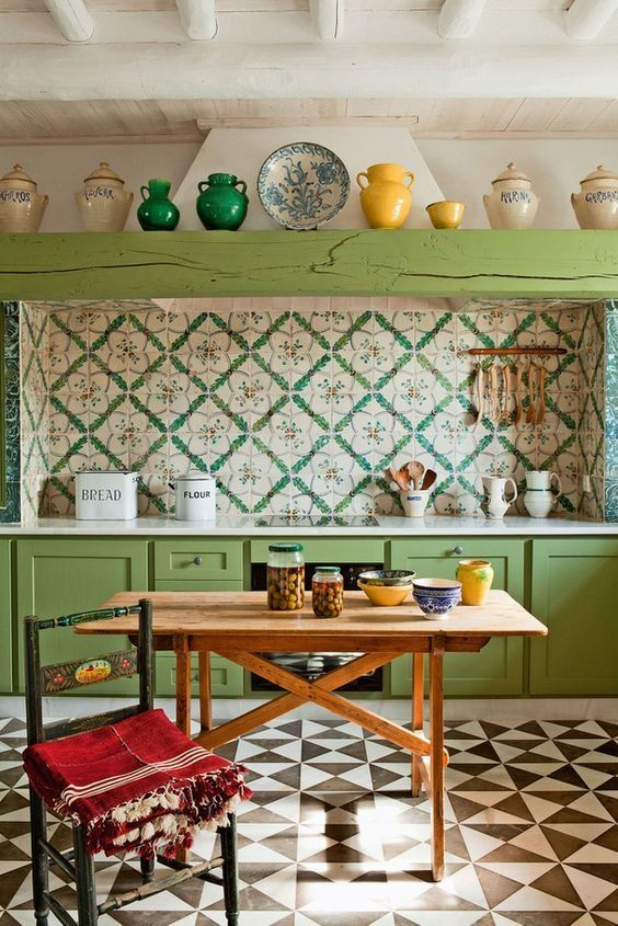 a bright boho vintage kitchen with green cabinets and a beam, a colorful tile backsplash and a bright mosaic floor