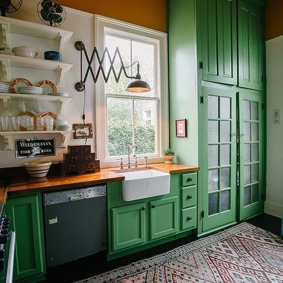 a bright green kitchen withwooden countertops and a colorful printed rug feels vintage