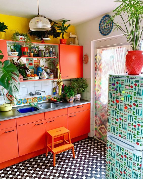 a bright orange kitchen with mustard walls, a tile backsplash and a printed fridge plus a printed curtain