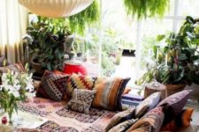 a bright sunken living room with colorful and patterned textiles and lots of potted greenery