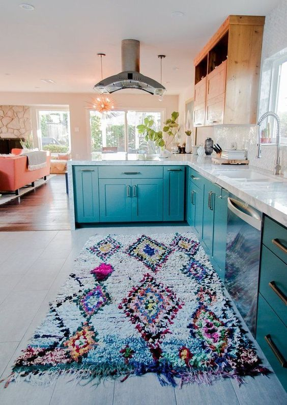 a bright teal kitchen with wooden uppers and a colorful fringe boho rug