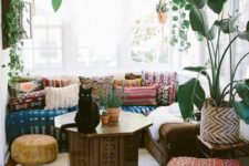a chic Moroccan living room with bright patterned textiles, a painted coffee table and potted greenery