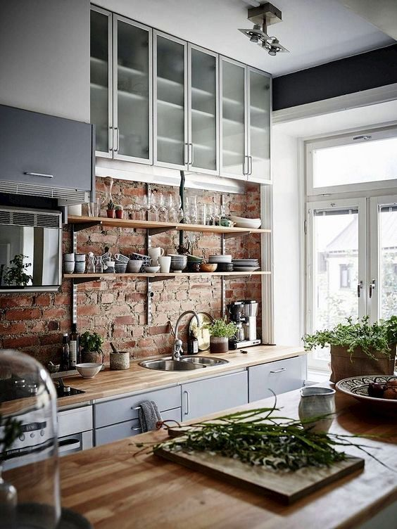 a chic Scandinavian kitchen with a brick wall, grey and frosted glas scabinets, butcherblock countertops and much light