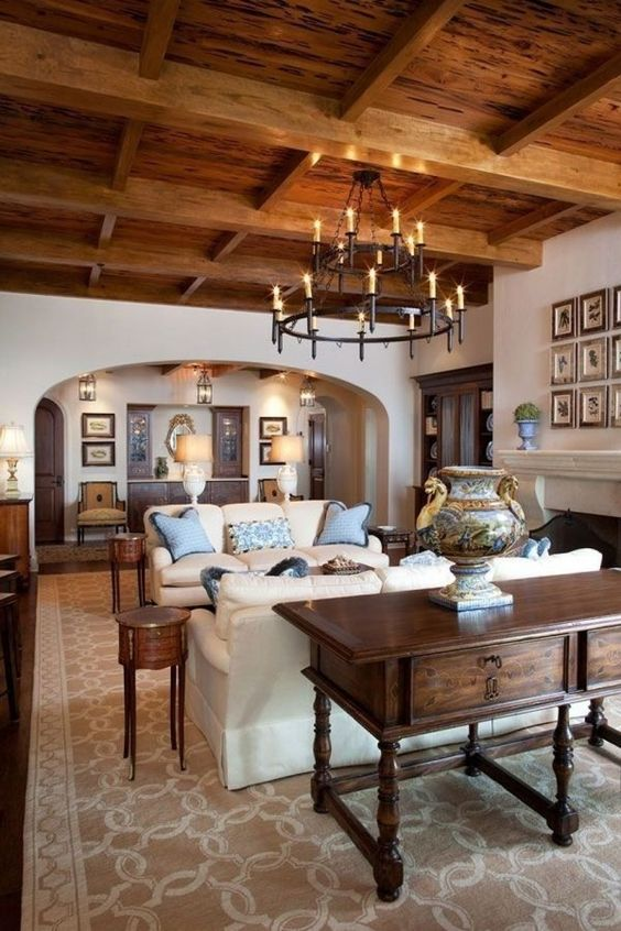 a chic and cozy rustic living room with rich stained furniture, a wooden ceiling and neutral sofas plus a fireplace