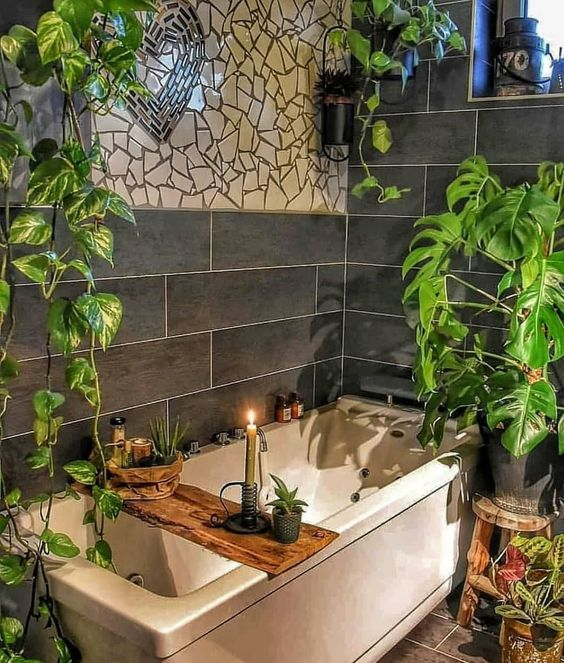 a chic boho bathroom with mosaics on the wall, potted greenery, a wooden caddy and candles