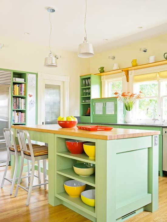 a chic farmhouse mint kitchen with light yellow walls, mint green cabinets, wood and stone countertops and yellow touches